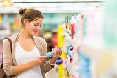 stock photo of grocery store  - Beautiful young woman shopping in a grocery store - JPG