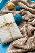 stock photo of blanket snow  - A gift to lie next to the coil bright filaments and blanket knitted on blue background - JPG