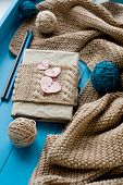 stock photo of blanket snow  - One Old Notebook In Knitted Cover With Felt Hearts Lie Next To The Coil Bright Filaments And Blanket - JPG