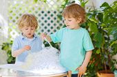 foto of experiments  - Two adorable friend boys making experiment with colorful soap bubbles and water outdoors - JPG