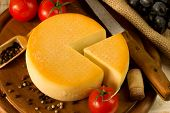 picture of meals wheels  - Cheese wheel on a wooden cutting board - JPG