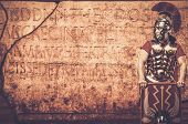 stock photo of writing  - Roman legionary soldier in front of  wall with ancient writing  - JPG