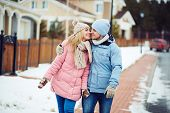 foto of sweetheart  - Young sweethearts walking along urban houses in winter - JPG