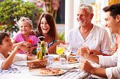 image of multi-generation  - Multi Generation Family Eating Meal At Outdoor Restaurant - JPG