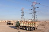 stock photo of voltage  - High voltage power lines and trucks in the desert of Kuwait Middle East - JPG