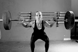 picture of jerks  - female athlete is lifting a barbell at the gym - focus on the woman ** Note: Visible grain at 100%, best at smaller sizes - JPG