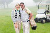 stock photo of buggy  - Happy golfing couple with golf buggy behind on a foggy day at the golf course - JPG