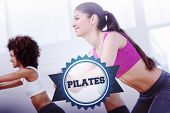 pic of pilates  - The word pilates and cheerful fitness class doing pilates exercise against badge - JPG
