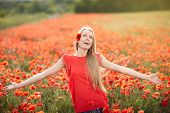 picture of poppy flower  - Lovely woman feeling happy on the poppy flower field. Beautiful woman in happiness and elated enjoyment with arms raised outstretched up enjoying nature, summertime leisure concept.