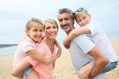 picture of piggyback ride  - Parents giving piggyback ride to children at the beach - JPG