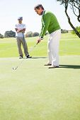 foto of take off clothes  - Golfing friends teeing off at the golf course - JPG