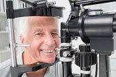 stock photo of slit  - Portrait of happy senior patient using slit lamp at clinic - JPG