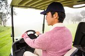 foto of buggy  - Golfer driving his golf buggy at the golf course - JPG