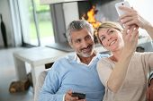 picture of maturity  - Mature couple at home having fun using smartphone - JPG