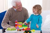 stock photo of preschool  - Grandpa and preschooler playing with building blocks - JPG