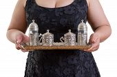 pic of serving tray  - Woman serving a tray laden with an ornate metal tea set as she asks  - JPG