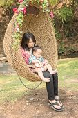 image of mother baby nature  - young mother holding baby on rattan swing - JPG