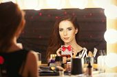 stock photo of makeup artist  - Portrait of a beautiful woman with gift box near a makeup artist mirror - JPG