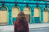 image of board-walk  - A young woman is walking on the street in a city and is looking at a boarded up building - JPG