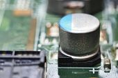 picture of capacitor  - macro capacitor on green circuit board background - JPG