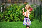 foto of blowers  - little girl play with bubble blower on green lawn - JPG