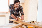 image of carpenter  - Confident young male carpenter working with wood in his workshop