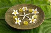 picture of gardenia  - Five gardenia flower with candle in wooden bowl ,starfish on banana leaf texture   - JPG