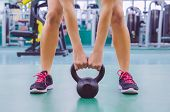 pic of health center  - Closeup of beautiful woman ready to lift black iron kettlebell in a crossfit training on fitness center - JPG