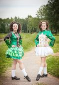stock photo of cross-dress  - Two young beautiful girl in irish dance dress and wig posing outdoor - JPG