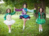 stock photo of wig  - Three young beautiful girls in irish dance dress and wig posing outdoor  - JPG