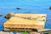 picture of floating  - Wooden floating work platform by the shore close to stones - JPG