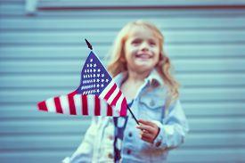 stock photo of waving hands  - Flying american flag in little girl - JPG