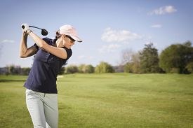 image of swing  - Close up of woman golf player swinging golf club - JPG