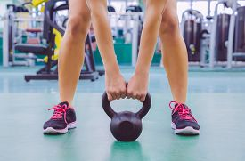 image of fitness  - Closeup of beautiful woman ready to lift black iron kettlebell in a crossfit training on fitness center - JPG