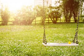 foto of swing  - Abandoned swing in warm sunny light with flowers in the spring season - JPG