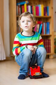 stock photo of daycare  - Active kid boy playing with wooden toy bus indoors - JPG